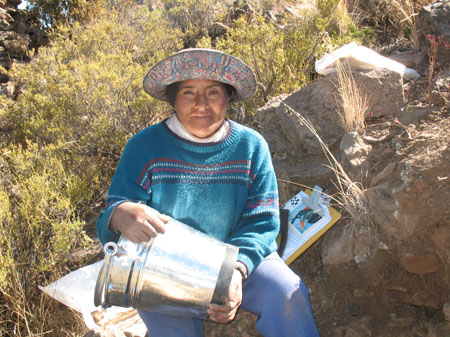 Guillerma sitting on a rock holding a metal bucket. She is smiling into the camera. There is a plastic bag to the left and a clipboard to the right. She is wearing a teal sweater with red, white, pink, and blue stripes across the chest. She is also wearing jeans and a at with a lots of colors on the bottom of the rim of the hatt. There are shrubs behind her.