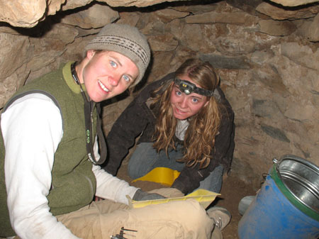 Cat and Emily are crouched in a small rounded and closed space made of laid brown stones. There is blue bucket with a green rim that is metal inside. There is a yellow tray of dirt between Cat and Emily and they both have their hands in it. Cat is wearing a white long sleeved shirt, green vest, khaki pants, sunglasses on the back of her neck with the strap hanging down in front, and a gray winter hat. Emily is wearing a dark gray jacket, jeans, and a headlamp. She has a headlamp on her forehead.
