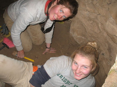 Cat is Susan are underground in a space with brown laid stones. Cat is on her knees and is leaning onto her hand. Susan is laying down. Cat is wearing a white longsleeved shirt, a red tshirt below the white, khaki pants, and sunglasses around her neck on a black strap. Her brown hair is pulled back. Susan is wearing a gray tshirt with green lettering, a blue long sleeves shirt under that, and khaki pants. She has blonde hair in a bun.