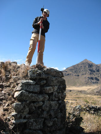 Tung is wearing a black jacket, a white baseball hat, and khaki pants. She is stanidn on top of a square-ish structure made of rocks. She is holding a mapping tool. The tool is a lens on a white striped stick. There is a hill in the background. The ground is grassy and rocky.