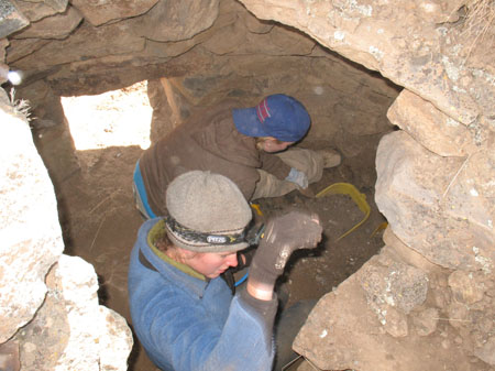 Catherine- awearing a blue jacket, gray beanie, and a headlamp- and Susan- wearing a gray jacket and blue baseball cap- are sitting under a structure made of rocks. Susan is using a yellow rectangluar bucket to scoop dirt.