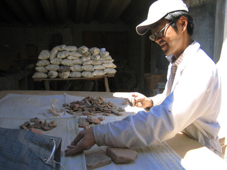 Hide is looking at ceramic shards on a wooden table with a white cloth on it. There are large pieces in front of him and a pile further down on the table.He is reaching into a cloth bag and smiling. In the background there is a table with a pile of full white cloth bags. There is sunlight on almost all of Hide, but the room is dark. Hide is wearing a shirt with red and blue lines making a square pattern, a white jacket, glasses, and a white baseball cap.