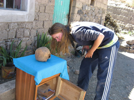 Emily is leaning down to look at a skull on a small wooden table outside. She is holding a camera and the strap is around her neck. There is a bleu cloth over the top of the table. There is a house behind Emily. It is made of gray stone, has a window with a gray outline around it, a door made of wooden planks painted teal blue, and plants lining the path in front of the house. Emily is wearing a gray sweatshirt, a yellow shirt, and black pants with the three white lines down the side.