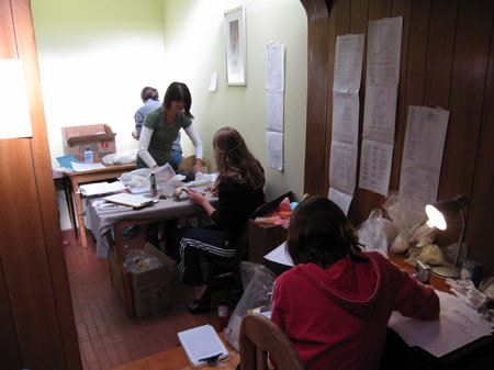 There are three small tables in a hallway. The first table has papers, clear bags of soil, a silver camera, and a black lamp. The person at this table has a red hoodie and long dark hair. At the next table Tiffiny and Emily are looking at skull fragments that had been wrapped in paper. There are two brown clipboards with paper on this table as well. Emily is sitting on the side closest to the camera- face away- and Tiffiny is standing on the other side facing the camera. Emily is wearing a black jacket and black pants with white stripes down the side. Tiffiny is wearing a long sleeved white shirt and a green short sleeved shirt. She has chin length brown hair. There is someone standing at the last table. This table has a box, a white bottle of glue with a blue lid, and something wrapped in paper. This person is wearing a gray jacket and jeans. They have dark hair pulled back. The wall to just before the middle table is vertical wooden panels and the rest is plain yellow. There are various printouts taped to the walls.