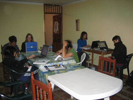 Six people sitting in a room, five of them have laptops in front of them and are doing data entry. Katie, Matt, Emily, and probably Mirza are sitting at a long white table. The end with the people sitting at it as a table cloth with a white background, green leaves, white flowers, and blue flowers on it. Katie is on a gray laptop. She is wearing a black jacket and blue pants with white stripes down the side. She has shoulder length brown hair. Matt has a laptop in his lap. He is wearing a gray tshirt and glasses. He has messy short brown hair and a brown beard. Emily is looking into the camera behind a laptop with a blue back. She is wearing a black jacket and has shoulder length light brown hair. The person who is probably Mirza is looking at a pile of papers in front of her and has one hand in her brown hair. She is wearing a green shirt and her hair is in a bun. Tiffiny and Chris are at a small wooden table. Tiffiny is looking at a black laptop. She is wearing a blue shirt and black pants. She has shoulder length brown hair. Chris is looking to the left of the photo and is front of a black laptop. Chris is wearing a black jacket, glasses, and jeans. Chris has short brown hair.