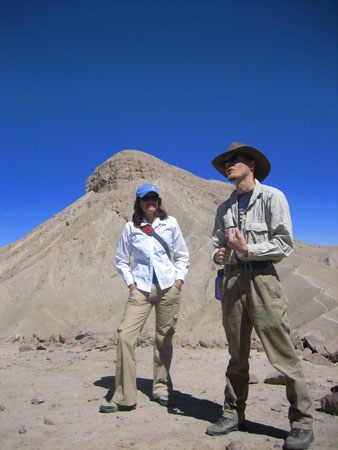 Donna and Ryan are standing in front of a hill made of either sand or finely ground rock. There is a large rock coming out of the top. Ryan is looking off to right past the camera and Donna is looking at him. The sky is bright blue. Donna is wearing a white button up, khaki pants, sunglasses, a blue baseball cap, and a strap across her body with a red shoulder pad. She has shoulder length dark hair. Ryan is wearing a blue tshirt, gray long sleeved shirt, dark khaki pants, and a brown cowboy hat. He has a purple water bottle clipped on his belt.