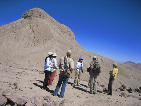 Donna is talking to a crowd of six people- including Ryan who is concealed. They are standing in front of a hill made of either sand or finely ground rock. There is a large rock coming out of the top. The person on the far right is wearing a white longsleeved shirt, black pants, a beige cap. They have long dark hair and is holding a green bag. The next person is wearing a long white sleeved shirt, red pants, and a khaki hat. They have short dark hair and a brown walking stick. The next person is wearing a brown tshirt, jeans, a brown-ish baseball cap, and a yellow bag with a black strap across their body. They have light brown hair in a bun. The next person is Donna, who is wearing a white shirt, khaki pants, and a blue baseball cap. She has shoulder length brown hair and is holding a blue water bottle. Ryan is behind the next person but you can see one leg in dark khaki pants and a purple water bottle. The person in front of Ryan is wearing a brown long sleeved shirt pushed past their elbows, dark khaki pants, a black backpack, and a brown baseball cap. The person on the far left is wearing a yellow tshirt, black pants, a brown hat, and black bag over their shoulder.