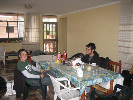 "Someone- who might be Chris- and Matt are sitting at a wooden table with a white table at the end of it. The wooden table has a table cloth with blue flowers, green leaves, and white flowers. There are varying sizes of glasses on the table. Possibly Chris- on the left- is smiling into the camera and is wearing a green shirt with white letters that may read ""Michigan,"" a gray long sleeved undershirt, and jeans. He has short brown hair. Matt is wearing a gray tshirt, a black jacket and glasses. He has short messy brown hair and a facial jair."