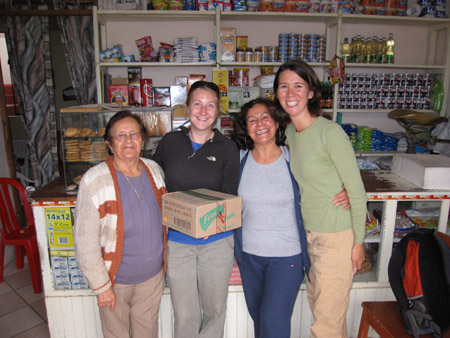 Eloise, Beth, a person, and Tiffiny are standing in front of a counter at a store. They are all smiling into the camera. Beth is holding a cardboard box. The counter is white and has windows with goods behind it. There are white shelves behind the counter with various other goods on it. There is a blue curtain behind the counter on the left. Eloise is wearing a blue shirt, glasses, a silver necklace, and khakis. She is also wearing a white, gray, and orange striped sweater. She has chin length dark hair. Beth is wearing a blue tshirt, black jacket, black sunglasses on her head, and gray pants. Her blonde hair is in a bun. The next person is wearing a gray tshirt, blue jacket, and blue pants. Tiffiny is wearing a a light green long sleeved shirt and khaki pants. She has chin length brown hair.