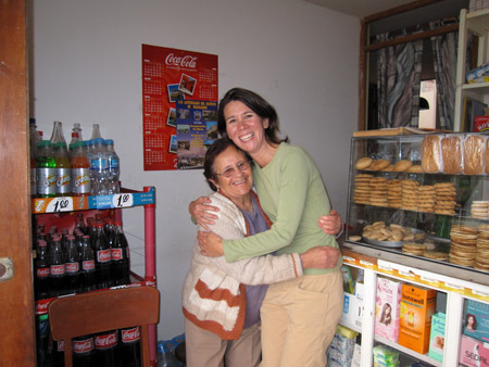 Eloise and Tiffiny are hugging each other, and smiling into the camera. To the right of them is a white counter with windows in with products in it. On top of it is a glass container with sweet treats in it. Behind the counter is a white shelf with more goods on it and a blue curtain. Behind the duo on the left is a red plastic shelf with Coke products on it. There is a red Coca-Cola calendar on the white wall behind them. Eloise is wearing a blue shirt, glasses, and khaki pants. She is also wearing a white, gray, and orange striped sweater. She has chin length dark hair. Tiffiny is wearing a light green jacket and khaki pants. She has shoulder length brown hair.