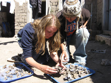 Emily and Sara are crouching on the ground looking at vertebrae on a blue tray. There is another tray on the left of the photo. There are stone pillars in the background and the edge of clothes hanging down. Emily is holding a verrt and Sara is pointing at it. Emily is wearing a blue sweatshirt and jeans. She has long light brown hair. Sara is wearing a blue tshirt with orange lettering, jeans, a brown jacket, and a white winter hat with brown llamas on it.