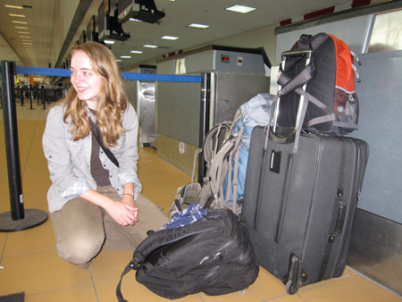 Emily is sitting down on the ground at the airport. She is smiling to the left of the photo. She is sitting next a pile of luggage- a black pack, a light blue backpack, and a gray suitcase with a red and black backpack on top of it. There are weigh stations for luggae along the right side of the photo. There are two black posts with a blue piece of fabric behind her. Emily is wearing a black tshirt, a gray button up, and khaki pants. She has shoulder length light brown hair.