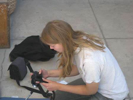Emily is holding a black camera and is crouching down on concrete squares. There is a black camera bag and a black jacket on the ground next to her. She is taking a picture of something on a dark blue cloth. She is wearing a white tshirt and and gray pants. She has shoulder length light brown hair.