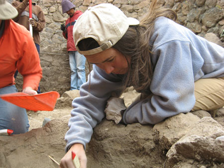 Tiffiny is squatting on the ground and is leaning into a dug out hole. There are two people leaning against the stonewall in the background and a person sitting beside Tiffiny holding an orange shovel. The person in the back right is wearing a red shirt with a black stripe across the chest, jeans, black gloves, and a purple hat. The person in the back left- whose face you can't see- is wearing a brown shirt with a white stripe across the chest and jeans. The person next to Tiffiny is wearing an orange jacket, jeans, and a brown hat. You can't see their face. Tiffiny is wearing a blue sweatshirt, khaki pants, and a khaki baseball cap.
