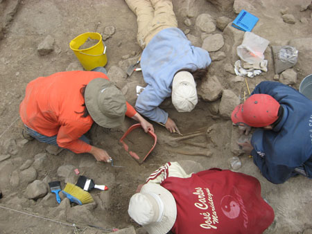 Tiffiny and three other people are excavating a grave, but only the legs can be seen. There are three brushes of different shapes and colors in the bottom left corner. There is a yellow bucket filled with dirt between Tiffiyn and the person on the left. The person on the far right is wearing a blue jacket and and red baseball cap. The person in the bottom of the photo is wearing a red jacket with white letters in cursive and a white bucket hat. The person on the left if wearing an orange jacket, jeans, and a gray-ish brown bucket hat. Tiffiny is wearing a blue sweatshirt, khaki pants, and a khaki baseball cap.