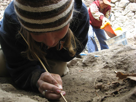 Sara is crouched very close to the rocky ground. She is holding a thin wooden stick. There is someone in the background is scooping dirt into a bucket. This person is wearing a red jacket with white sleeves, jeans, and a red baseball cap. Sara is wearing a navy sweatshirt with orange lettering and a brown and white striped