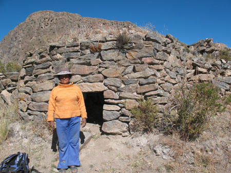 Guillermina is standing outside a round structure made of large flat-ish stones of varying shapes and colors. She is looking into the camera. This possibly where the guinea pigs are. There are shrubs around the structure and there's a hill in the background. Guillermina is wearing a orange long sleeved shirt, blue pants, and a brown hat.
