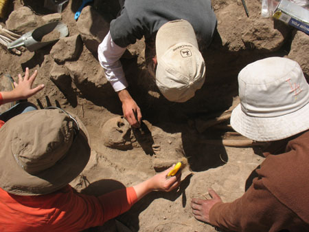 Ellen, Tiff, and Hector are excavating a skeleton out of rocky ground. Tiffiny (middle) is wearing a white long sleeved shirt, a gray tshirt, and a beige baseball cap. Ellen (presumably left) is wearing a red jacket, a brown hat, and jeans. Hector (presumably left) is wearing a white hat and a brown shirt.