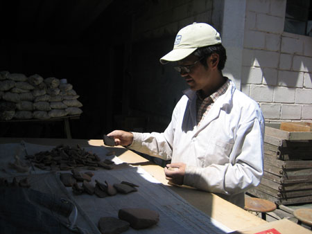 Hide is holding a large brown ceramic shard in his hand. There is a large pile and a small pile of ceramic shards in various colors. Hide is in the sunlight but the table is not. Also in the dark, is a table covered with white bags. Hide is wearing a white shirt with red stripe, a white jacket, glasses, and a white hat. He has short black hair.