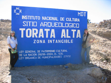 "Katherine and Kristina are standing on either side of a large blue sign with white lettering. The letters read ""Instituto Nacional de Cultura; Sitio Arqueologico; Torata Alta; Zona Intangible; Ley General de Patrimono Cultural; De La Nacion 28296-2004, Dl. 535.; Ley Organica de Municipal/Daies 27972."" ""MDT"" is written in the top right corner. ""Inc"" is written four times in a square. Katherine (right) is wearing a white long sleeved pushed past his elbows, black pants, and a white baseball cap. She is holding something green. She has shoulder length dark hair. Kristina K is wearing a short sleeved brown shirt, jeans, a green bag with a black strap around her neck, and light brown baseball cap with black sunglasses over it."