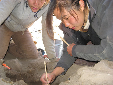 Katie is looking into a hole in the rocky ground. She is holding a thin wooden tool into the hole and the brush-part of a brush with a wooden handle. There is someone else looking into the hole behind her. There is a bucket in the background. Katie is wearing a white scarf with a light brown and dark brown stripe in the center, a black jacket, and a gray jacket. Her brown hair is pulled back. The person in the backround is wearing a gray jacket and khaki pants.