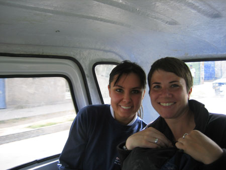 Kristina and Chris are sitting in a car. They are both smiling into the camera. There is large window to the left and a small one. Part of the back window can also be seen. The rest of the inside of the car is white. Kristina is wearing a white collared shirt and a gray sweatshirt. She has brown hair is pulled back. Chris is wearing a black jacket. Chris' knees are pulled to their chest under a black skirt. They are wearing a black jacket with a hood and two silver rings. Chris has short brown hair.