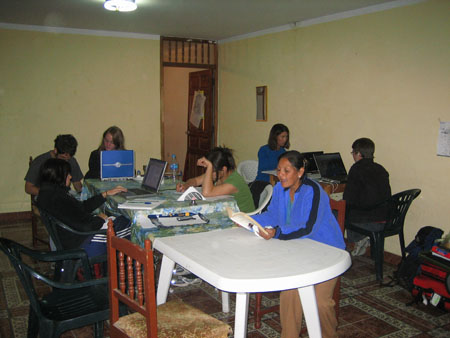 Seven people sitting in a room, five of them have laptops in front of them and are doing data entry. Katie, Matt, Emily, possibly Mirza, and Gloria are sitting at a long white table. The end with the people sitting at it as a table cloth with a white background, green leaves, white flowers, and blue flowers on it. Katie is on a gray laptop. She is wearing a black jacket and blue pants with white stripes down the side. She has shoulder length brown hair. Matt has a laptop in his lap. He is wearing a gray tshirt and glasses. He has messy short brown hair and a brown beard. Emily is looking into the camera behind a laptop with a blue back. She is wearing a black jacket and has shoulder length light brown hair. Possibly Mirza is looking at a pile of papers in front of her and has one hand in her brown hair. She is wearing a green shirt and her hair is in a bun. Gloria is wearing a blue jacket with black stripes down the side. Her black hair is pulled back. Tiffiny and Chris are at a small wooden table. Tiffiny is looking at a black laptop. She is wearing a blue shirt and black pants. She has shoulder length brown hair. Chris is looking to the left of the photo and is front of a black laptop. Chris is wearing a black jacket, red jeans, glasses, and jeans. Chris has short brown hair.