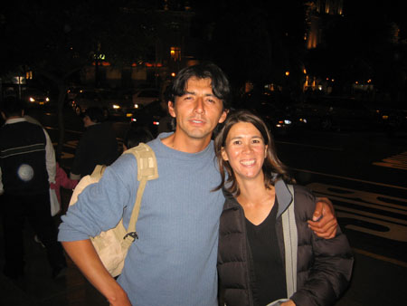 Abel and Tiffiny are standing on the side walk at night and smiling into the camera. Their arms around each other. There are people behind them and cars in the street. Abel is wearing a blue sweatshirt and light brown bag over his shoulder. He has short black hair. Tiffiny is wearing a black tshirt, black jacket, and a gray bag over her shoulder.