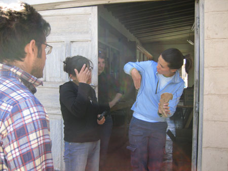Matt, Mirza, and Chris are looking at Tiffiny who is holding a pelvis as well as gesturing with her hand. Her hand is flat, with her thumb tucked behind it, next to her arm pit, and pointing down. She is looking at Mirza. Mirza is scratching her forehead. Tiffiny is standing in a doorway made for two doors- only one is open. Chris is halfway behind the closed door inside. This door is white and made of wood. The wall is made of beige planks of wood. Matt is wearing a red, white, and blue plaid shirt as well as glasses. He has short brown hair and facial hair. Mirza is wearing a black jacket, jeans, and glasses. Her brown hair is in a bun. Chris is wearing a black shirt and black pants. Chris's hair is shrot and brown. Tiffiny is wearing a white tshirt, a light blue jacket, and navy pants. Her brown hair is in a ponytail.
