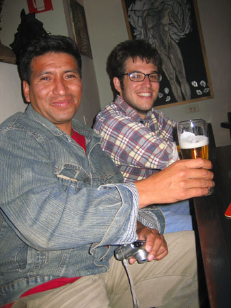 Manuel and Matt are smiling into the camera and sitting at a wooden table. The room is dark, but you can see a painting of a person the color white against a black background on the white wall. Manuel is holding up a beer in a clear glass in front of him and is holding a silver camera in his other hand. Matt's arms are crossed. Manuel is wearing a red tshirt, a jean jacket, and khaki shorts. He has short black hair. Matt is wearing a light blue, dark blue, white, and red plaid shirt as well as glasses. He is also wearing jeans. He has short brown hair and facial hair.