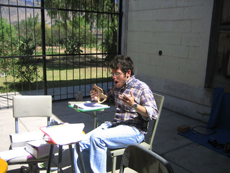 Matt is holding a pelvis in one hand, gasping, and holding his other hand in a shrug- he has found a cutmark. He is sitting in a gray chair at a very small table with a green clipboard on it. In the foreground, there is a black chair at another small table with a red clipboard at it. There is a low small table bewteen the other two with a stack of papers and a white box. There is a black fence in the background that you can see green grass and trees through. There is a white brick wall in the back right. Matt is wearing a red, black, and white plaid shirt. He is wearing glasses and jeans. He has brown short hair and facial hair.