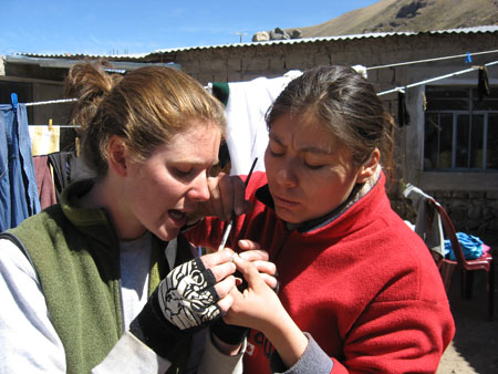 Cat and Mirza are holding something and looking at it. Mirza is holding a small black brush to it in her other hand. There is a house made of stone with white windows and a tin roof in the background. As well as a clothes line. Cat is wearing a gray sweatshirt, green vest, and black gloves with white art on it. He brown hair is pulled back. Mirza is wearing a red jacket. Her brown hair is held back.