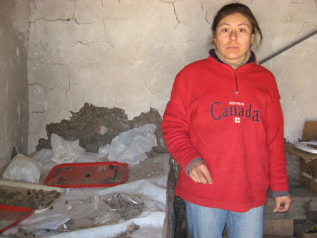 "Mirza is standing next to a table with bones and dirt on it. She is looking into the camera. There are two red trays and a tan tray with small bones on them. There are plastic bags on the table. She is wearing a tan undershirt, jeans, and a sweatshirt that reads ""Canada"" in blue letters."