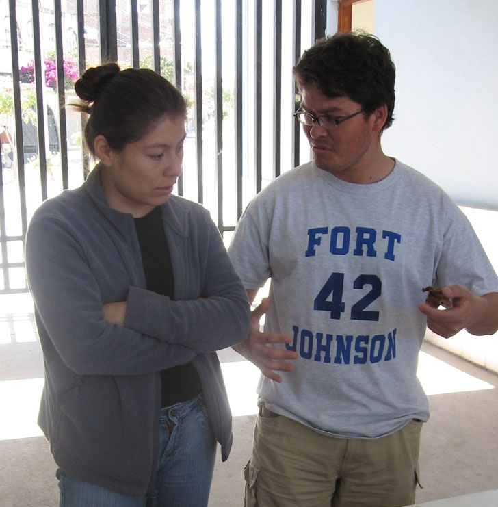 "Mirza and Roberto are talking. They are standing in the shade but the sun is coming through a black metal gate behind them. Mirza is wearing a black tshirt, gray jacket, and jeans. Her brown hair is in a bun. Roberto is wearing a gray shirt that says in blue lettering, ""Fort; 42; Johnson"" as well as kahki pants. He wears glasses. He has short brown hair."