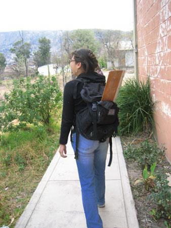 Mirza is walking away from the camera with a wooden measuring tool sticking out of her black backpack. The tool is a plank of wood with a small piece of wood on each side- one slides to measure how long femurs are. It is sticking out at an angle and you can not see the smaller pieces. She is walking on a sidewalk with grass and plants on either side. On the right there is a brick wall painted red with a circular white splotch. There is a white building in the distance on the right and a mountain in the background. You can't see Mirza's whole face, but from what you can see of the left side of her face there is the impression that she is smiling. She is wearing a black jacket, jeans, and glasses. Her black hair is pulled back.