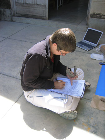 Chris is sitting on the ground, holding a mandible, and writing in a journal. There is the edge of a blue cloth in the photo as well as a gray laptop. The ground is made of large white-ish square stones. Chris is wearing a black jacket, red shirt, glasses, and khaki pants. Chris has short brown hair.
