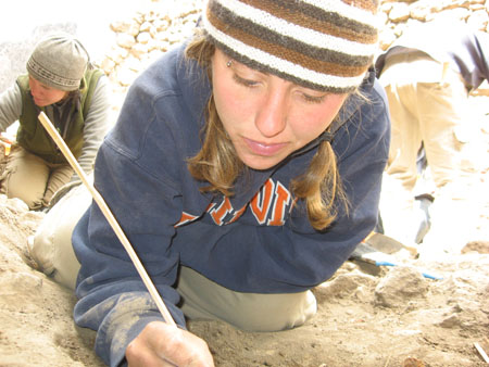 A close of up Sara crouching by an excavation that can't be seen. Cat is in the back on the left and someone's back is on the right. Sara is holding a small wooden tool into the hole. She is wearing a blue sweatshirt with orange letters with white outlines. She is also wearing khaki pants and a brown, black, and white beanie. She has a piercing in the eyebrow on the left. Her brown hair is in pigtails. In the background, Cat is wearing a gray shirt, a green vest, khaki pants, and a gray beanie. The other person is wearing a blue swearshirt and khakis.
