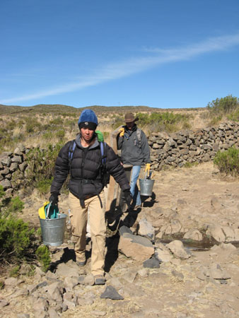 Tiffiyn and Travis are both carrying metal buckets with supplies in them towards the camera. They are both looking down. There is a short wall behind them made of gray stones. There are green shrubs scattered on both sides of the wall. There are small hills in the very distance. There are large brownish rocks by their feet. Tiffiny is wearing a black jacket, khaki pants, a backpack with blue straps, black gloves, and a blue beanie that is black around the edge. Travis is wearing a a gray jacket, jeans, yellow gloves, and a brown cowboy hat.