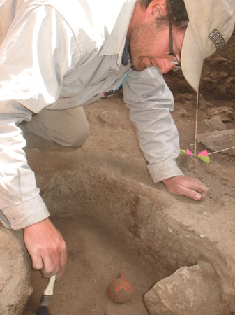 "Steve is kneeling over a rectangular hole with a rock in it and a small orange circular ceramic piece. He is holding a paintbrush with a white handle and black bristles. There is two pieces of white strings pulled into the distance with pink and green ties at the corner they make. Steve is wearing a white long sleeved shirt with different colored pens in the pocket, khaki pants, and a khaki baseball cap. You can see the letters ""Van"" in the word Vanerbilt on his hat. The letters are white and outlined in black."