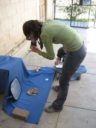 Tiffiny is standing over pelvis and taking a photo of it with a black camera. The pelvis is on a blue cloth that is propped up on something square to create a a background when a photo is being taken from the front. There is a brick holding down the fabric in the front of the image. Matt is sitting on the ground next to Tiffiny, writing on the notebook in his lap. The ground is large white stones and the wall is made of small white stones. Tiffiny is wearing a green long sleeved shirt, jeans, and gray shoes. She has shoulder length brown hair. Matt is wearing a black t shirt, jeans, and glasses. He has short brown hair that you can't see.