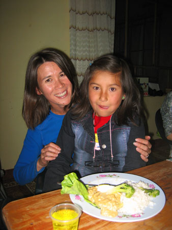Stephanie (right) is sitting in Tiffinys lap. They are both smiling into the camera. They are sitting at a wooden table. There is a plastic cup filled with yellow liquid and a white plate with pink flowers on the edge. There is white rice, broccoli, and a meat of some sort on the plate. The wall behind them is yellow. The window is divided into different panes by black metal. There is a white and brown curtain by the window. Tiffiny is wearing a blue shirt, and has shoulder length brown hair. Stephanie is wearing a red shirt and a black jacket. She has shoulder length brown hair.