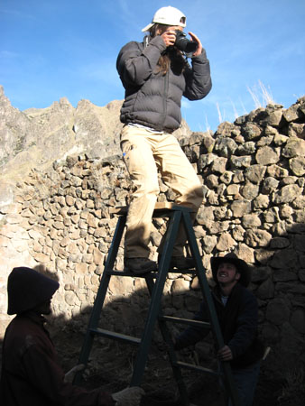 Tiffiny is taking a photo on top of a blue ladder. Saul and Travis are holding the ladder. Saul is looking at Travis and Travis is smiling up at Tiffiny. There is a gray stone wall behind them and a rocky peak on the other side of the wall. Tiffiny is wearing a black jacket, a backwards white baseball cap, and khaki pants. She has shoulder length brown hair. Saul is wearing a orange-y jacket, white gloves, and a brown hat. Travis is wearing a black jacket, jeans, and a cowboy hat.