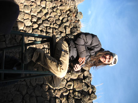 Tiffiny is sitting on top of a blue ladder and smiling into the camera. She is holding a black camera. There is a wall of gray and brown stones behind her. The sky is blue. Tiffiny is wearing a black jacket. khaki pants, and a backwards white baseball cap. She has shoulder length brown hair.