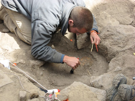 Travis is dusting off a portion of dirt surrounded by large gray rocks. There is a patch of on orange covered in dirt on the right of the grave. There is a string held into a rock with a piece of metal on the left side. Travis is wearing a blue jacket and khaki pants. He has buzzed brown hair.