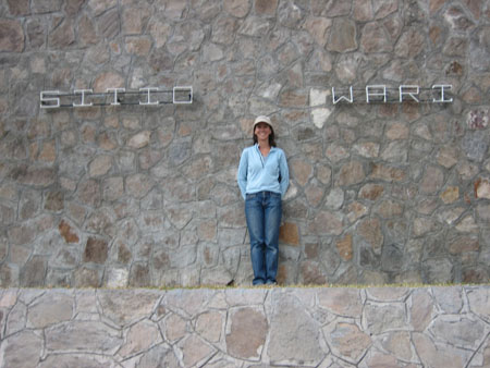 "Tiffiny is standing on a grassy spot that is on a foundation made by a stone wall. The back wall is also made of stones. There are two words written in metal letters on either side of Tiffiny. On the left is says ""Sitio"" and on the right it says ""Wari."" Tiffiny is wearing a blue jacket, jeans, and a white baseball cap. She has shoulder length brown hair."
