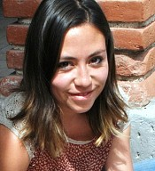Keitlyn is sitting outside in front of a red brick wall. She has shoulder length brown hair. She is wearing a red top with white dots and white lace sleeves.