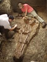Carrie Anne is sitting down next to a skeleton that is partially excavated from the dirt. She is looking down and to the right. There is another person wearing a white shirt next to the skeleton. Carrie Anne is wearing a pink tshirt, khaki pants, and brown shoes. Her blonde hair is shoulder length.