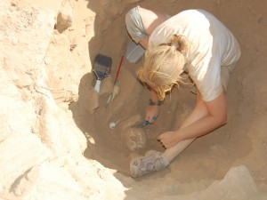 Beth is sitting in a deep sandy hole looking down at a skeleton she is excavating. She is wearing a white tshirt, khaki shorts, and gray shoes. Her blonde hair is in a ponytail. There are two brushes next to her- one is thin with a red handle and the other is wide with a gray handle.